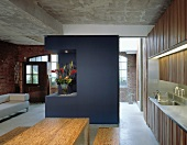 Open-plan living space in converted factory building with blue-painted partition