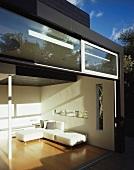 Geöffnete Terrassentüren mit Einblick in Designer Wohnraum eines zeitgenössischen Wohnhauses