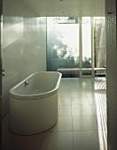 Minimalist bathroom with free-standing, white bathtub on tiled floor