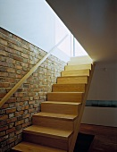 Modern wooden staircase with handrail on brick wall