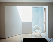 Bedroom with white shell chair in sunny anteroom leading to bathroom