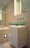 Extravagant glass sink on white base cabinet in front of marble-clad wall