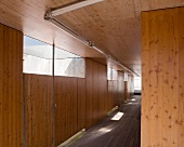 Wood-clad hallway with transom windows in wooden wall