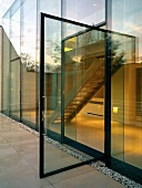 Open glass door leading to terrace of contemporary apartment building