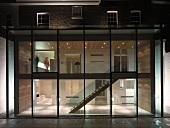 Contemporary extension with glass wall and view of illuminated, two-storey stairwell