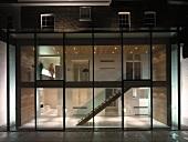 Zeitgenössischer Anbau mit Glasfront und Blick in beleuchteten mehrstöckigen Treppenraum