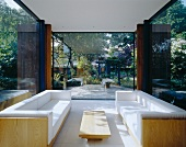 Sofa set with white upholstery in modern, glass-walled room with view of garden