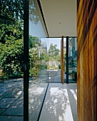 Contemporary building with glass wall and open door with view of terrace