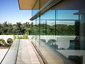 Encircling terrace against glass facade of contemporary house with view of garden
