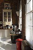 Seitenlicht durch Fensterwand einer Loftküche mit Sammlerstücken im Vintage-Stil