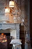 Weihnachtsschmuck an Zweigen vor Kaminfeuer und holzverkleideter Wand