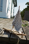 Small, home-made wooden boat with striped sail