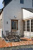 Sitzplatz mit Holzklappstühlen auf Ziegelterrasse vor weiss geschlemmtem Backsteinhaus