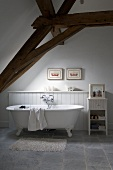 Free-standing, clawfoot bathtub under exposed roof structure