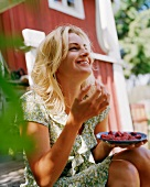 Young woman eating strawberries in garden