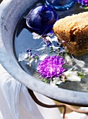 Washbasin with flowers and sponge in garden