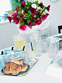 Cinnamon buns under a glass cloche and a summery bunch of flowers on a table
