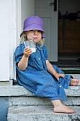 Girl with glass of milk sitting in front doorway