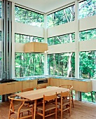 Kitchen with dining area in house made of glass and wood elements in forest