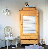 Wooden corner cupboard with glass door in child's bedroom