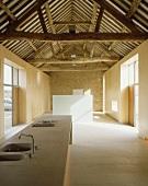 Im Designerstil ausgebauter offener Wohnraum mit Küchenbereich und Blick in alten Dachstuhl