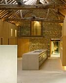 Im Designerstil ausgebauter offener Wohnraum mit freistehendem Küchenblock vor Natursteinwand
