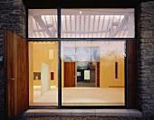 Blick durch Fensterfront in beleuchteten Innenraum