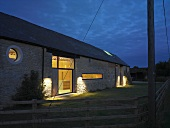Renovated farmhouse at dusk with illuminated windows