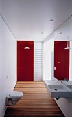 Narrow designer bathroom with wooden floorboards and red glass wall