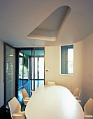 White dining table and chairs under suspended ceiling with cut-out