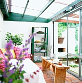Conservatory with wooden bench, sofa and shelves