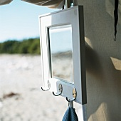 Mirror with coat pegs hanging on a tent