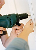 Screwing shelving battens to wall using cordless screwdriver