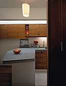 View into open-plan designer kitchen with concrete work surface on counter