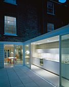 Courtyard with white tiled floor and view of illuminated kitchen in extension