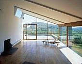 Sessel mit Fussschemel im leeren Wohnraum mit Panoramablick