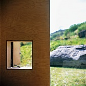 Wooden wall with window aperture and view of landscape