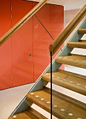 Staircase with wooden treads and view of fitted cupboards with red doors through glass balustrade