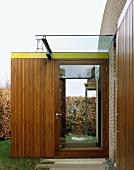 Glass front door in wood-clad porch extension