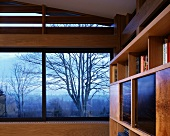 Detail of room with panoramic window and view of autumnal landscape