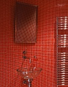 Glass washbasin and mirror on wall with red mosaic tiles