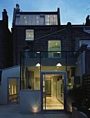 Zeitgenössischer Anbau am Wohnhaus mit Innenraumbeleuchtung in Abendstimmung