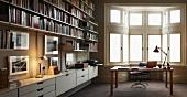 Moderne Bibliothek mit Schreibtisch vor Erker im traditionellen Stil