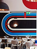 Restaurant with tables and chairs in front of boldly-coloured wall