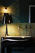 Detail of bathroom in half-light - table lamp with glossy lampshade on washstand with glossy surface