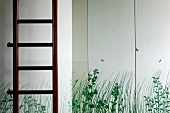 Detail of ladder in front of painted cupboard doors