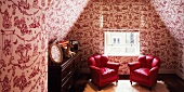 Attic room with red armchairs and wallpaper with erotic pattern