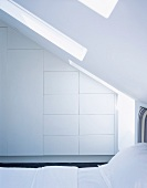 White, fitted, designer wardrobes and bed under sloping ceiling with skylight