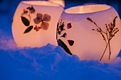 Tealight holders with pressed flowers in snow