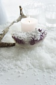 Candle holder made of ice with frozen berries